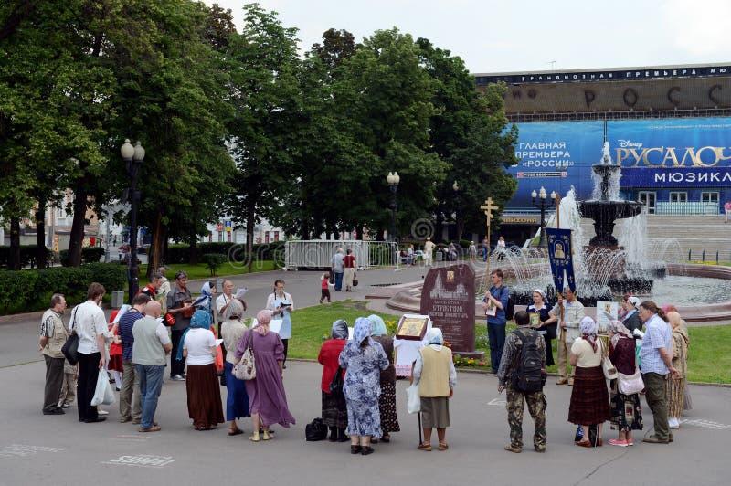 Bön av ortodoxa troenden nära en minnesvärd sten i heder av den passionerade jungfru- kloster på den Pushkin fyrkanten i Moskva royaltyfria foton
