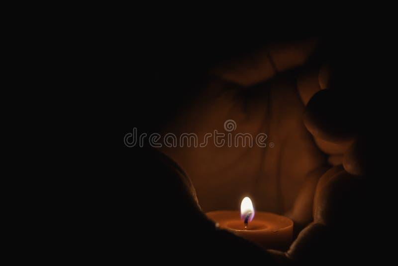 Bön - stearinljus i händer royaltyfri fotografi