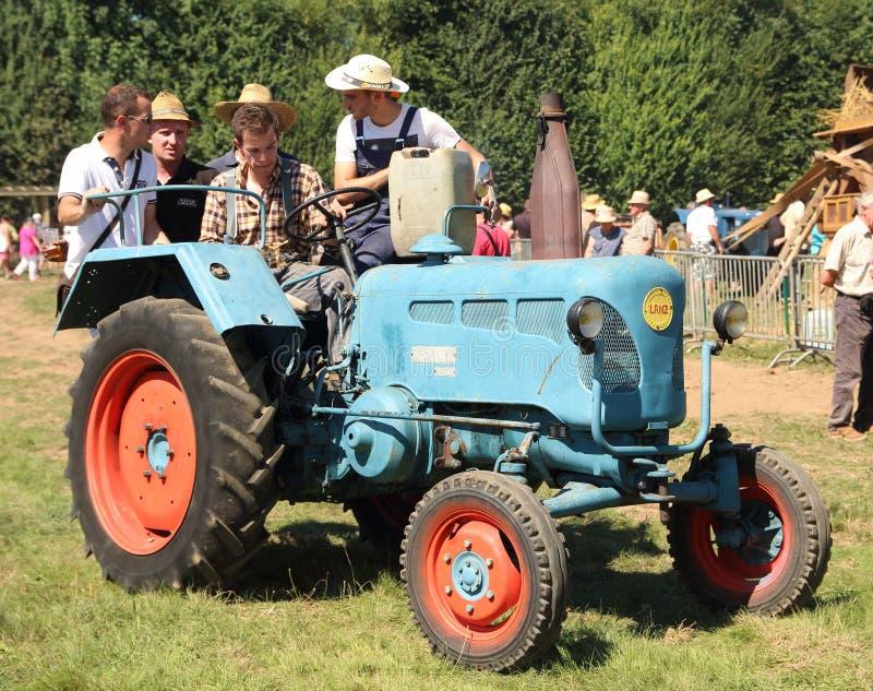 Bönder på en gammal traktor royaltyfria bilder
