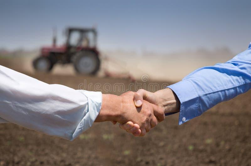 Bönder som framme shking händer av traktoren fotografering för bildbyråer