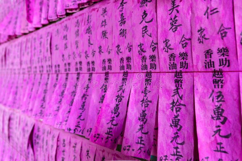 Bönflaggor eller snedsteg av en rosa färg med namn i kinesiskt svart färgpulver i den Thien Hau templet, Cho Lon, Ho Chi Minh Ci, royaltyfria bilder