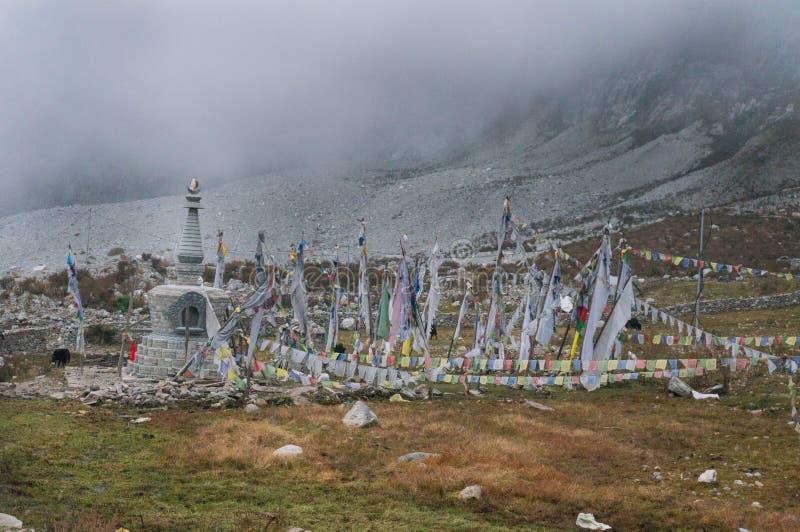 Bönflaggor och buddistisk stupa på den Langtang byn Tibetan region arkivbilder