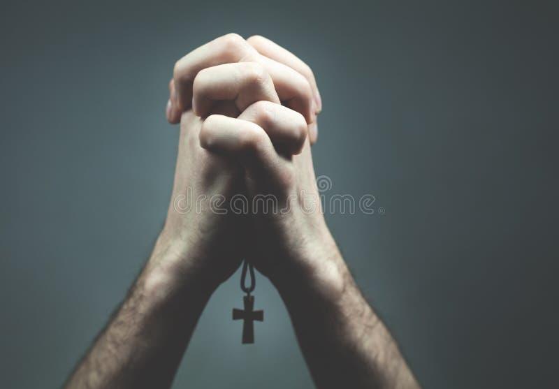 Bönhänder med det kristna katolikkorset arkivfoto