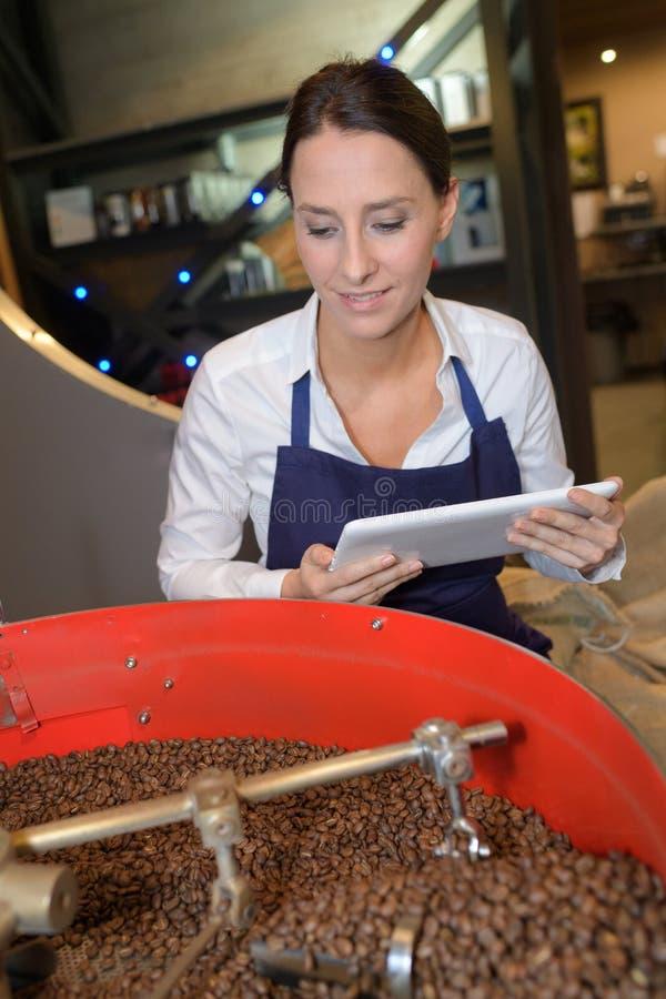 Bönor för kaffe för hållande minnestavla för kvinna hållande ögonen på som grillas arkivbilder