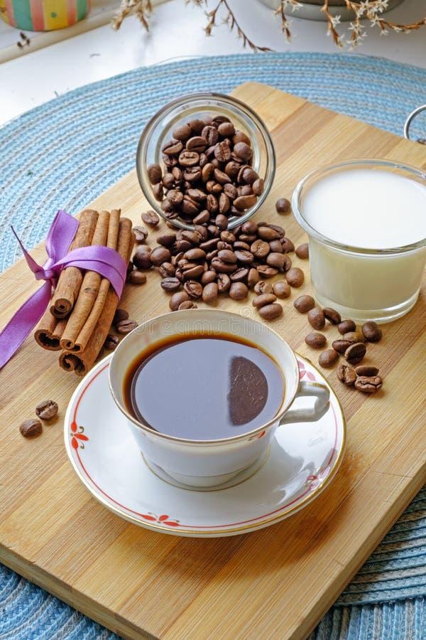 Bönor för kaffekopp mjölkar och för ståendesida för kanelbruna pinnar sneda bollen royaltyfria foton