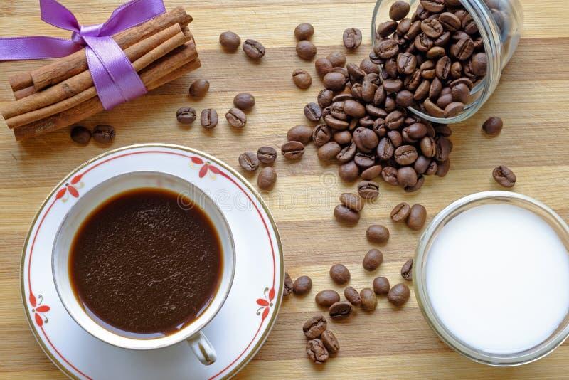 Bönor för kaffekopp mjölkar, och kanelbruna pinnar landskap den bästa skörden royaltyfria bilder