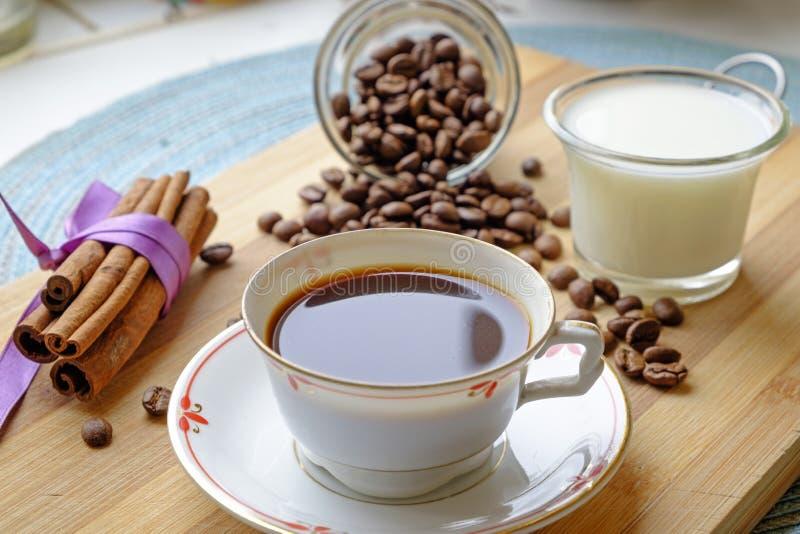 Bönor för kaffekopp mjölkar, och kanelbruna pinnar landskap den oskarpa sidan arkivbild
