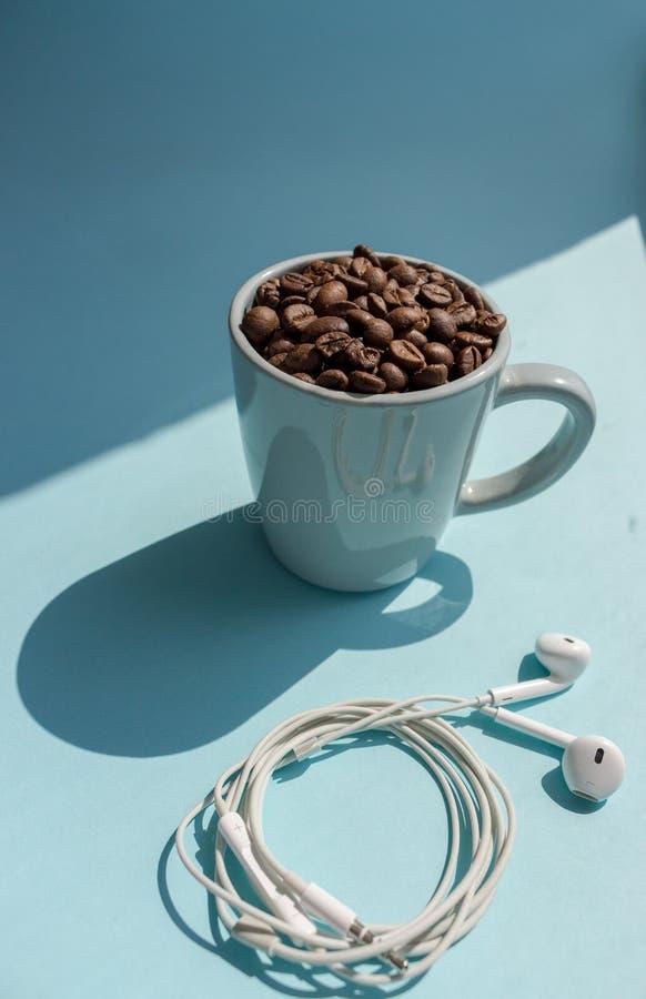 Bönor för svart kaffe i blåttkopp- och vithörlurar på blå bakgrund med solljus skuggar Morgondrinkbegrepp royaltyfria bilder