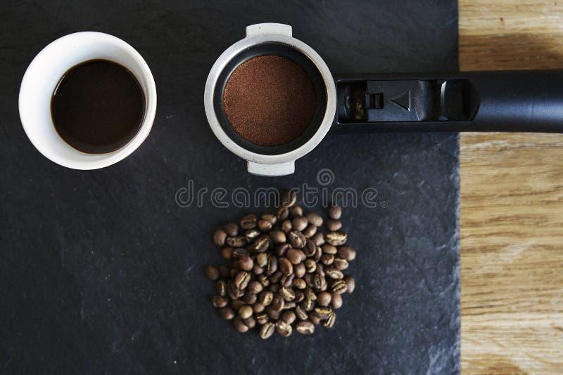 Bönor och grundat kaffe i filterhållare i svart stounbräde från över arkivbild