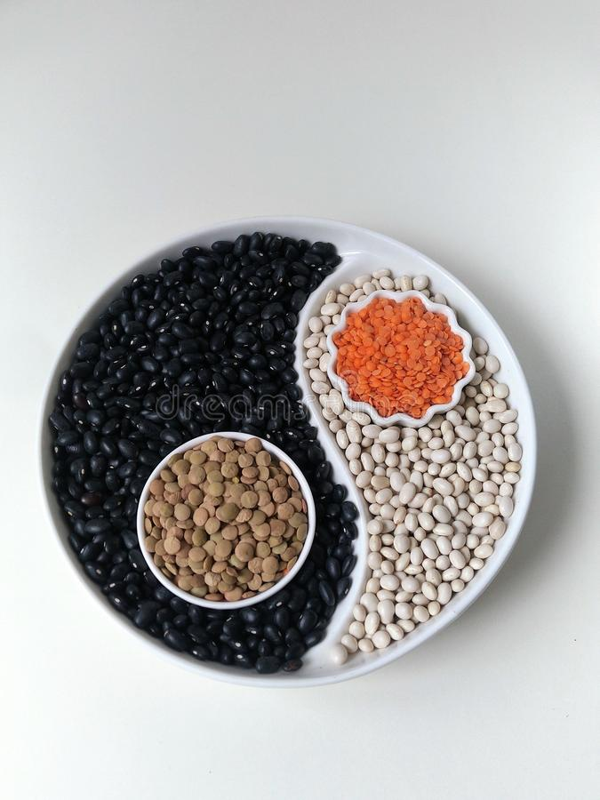B?nor och linser p? sk?rmen med ett jobbkort i form av Yin Yang flatley Foodfoto royaltyfri fotografi
