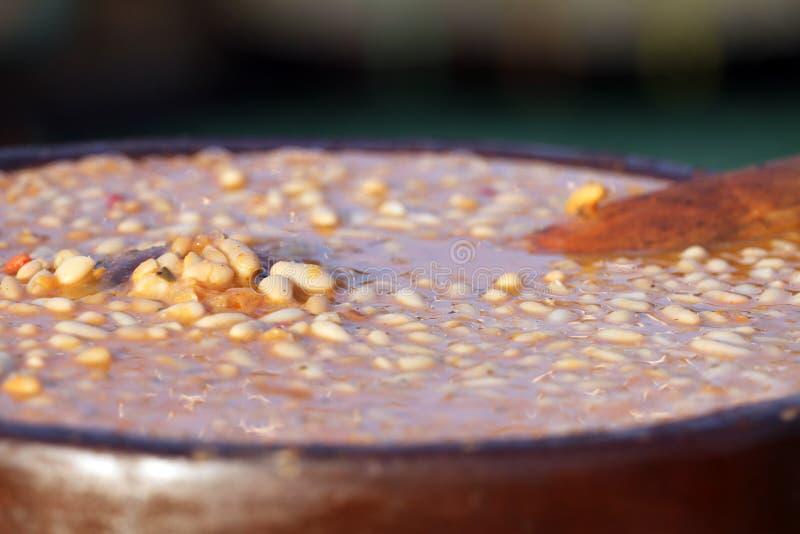 bönor stew white Lergodseldfast form med ragu för vita bönor Ragubakgrund Lagad mat bönaragu på ett dagsljus utanför Carbohyd arkivbilder