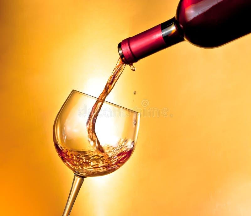 Börja fyllnads- rött vin i det vippade på exponeringsglaset arkivbild