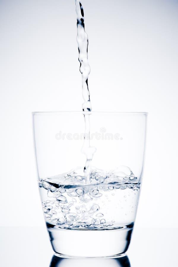 Börja påfyllning ett exponeringsglas med rent vatten och bubblor royaltyfria bilder