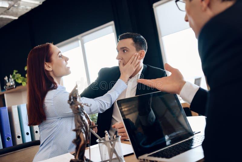Böse Frau schlägt das überraschte Ehemanngesicht und sitzt an Rechtsanwalt ` s Tisch, um Heirat aufzulösen lizenzfreies stockbild