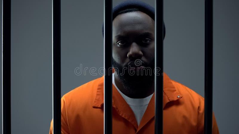 Böser Gefangener, der sich durch Bars Kameras anschaut, bedauert das Verbrechen lizenzfreie stockbilder