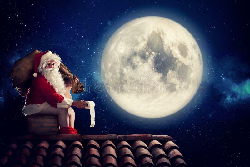 Böses Santa Claus-Heck in einem Kamin unter Mondschein als schlechtem Kindergeschenk Alternativer Weihnachtsurlaubsgrüßebeitrag stockfotos