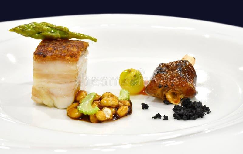 Bötfälla äta middag huvudrätten: Frasig grisköttbuk med Bean Stew och BBQ P arkivfoton