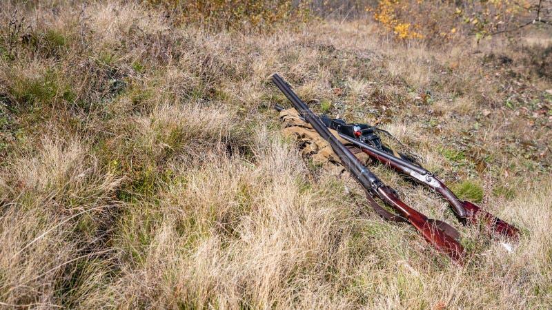 Búsqueda de fuentes y del equipo en la tierra en el concepto del bosque: la temporada de caza comenzó fotografía de archivo