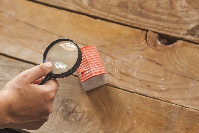 Búsqueda de un nuevo hogar, concepto de las propiedades inmobiliarias El hombre que mira a la casa miniatura del juguete a través fotografía de archivo libre de regalías