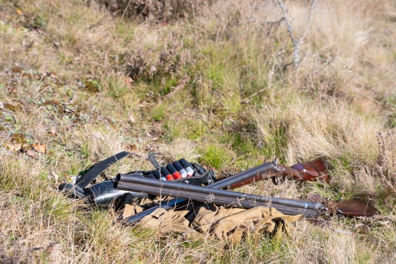 Búsqueda del engranaje en la tierra en el concepto del bosque: la temporada de caza comenzó fotos de archivo