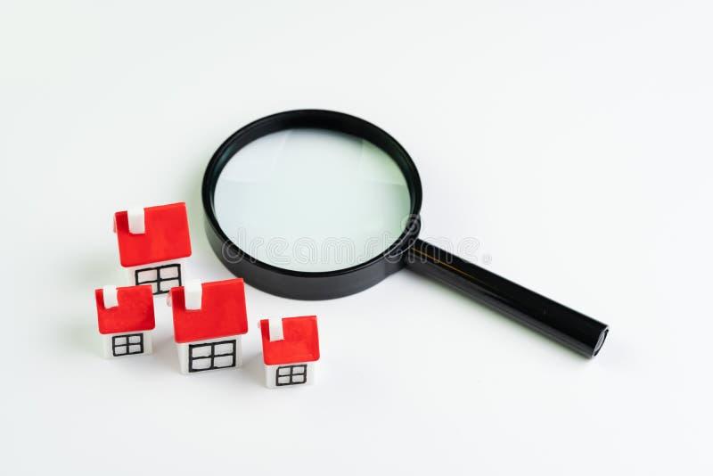 Búsqueda para la casa y préstamo hipotecario, propiedades inmobiliarias o concepto del préstamo de hipoteca, lupa con el grupo de foto de archivo libre de regalías