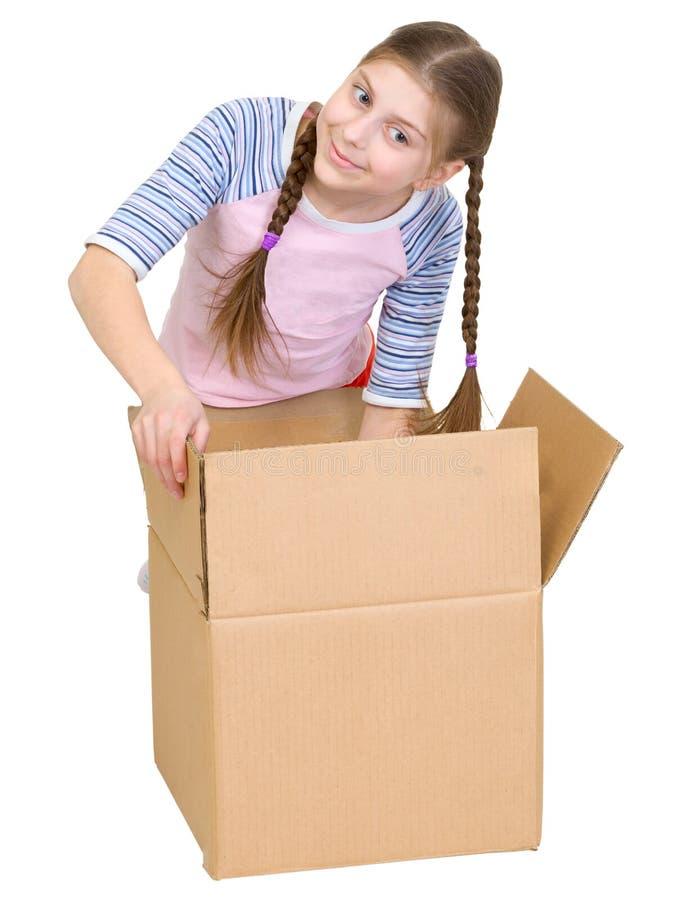Búsquedas de la muchacha en una caja de cartón foto de archivo