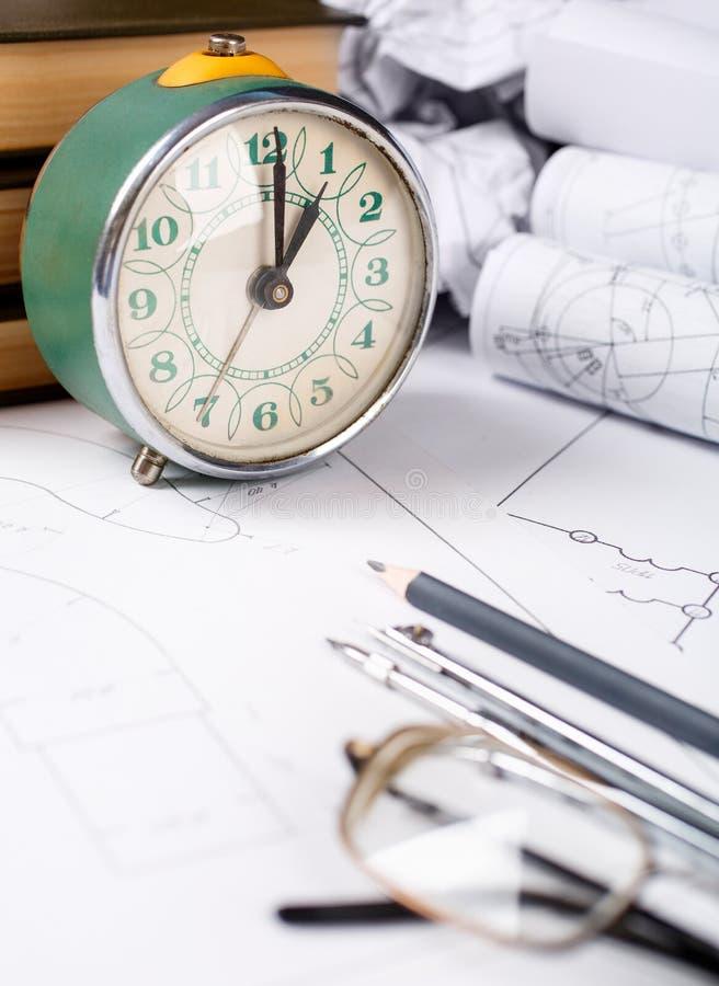 Bücher auf Architektur, einige zerknitterte Zeichnungen, Gläser auf dem Tisch im Architekten stockfotografie