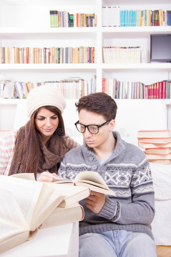 Bücher des glücklichen Paars Lesezu hause lizenzfreie stockfotografie