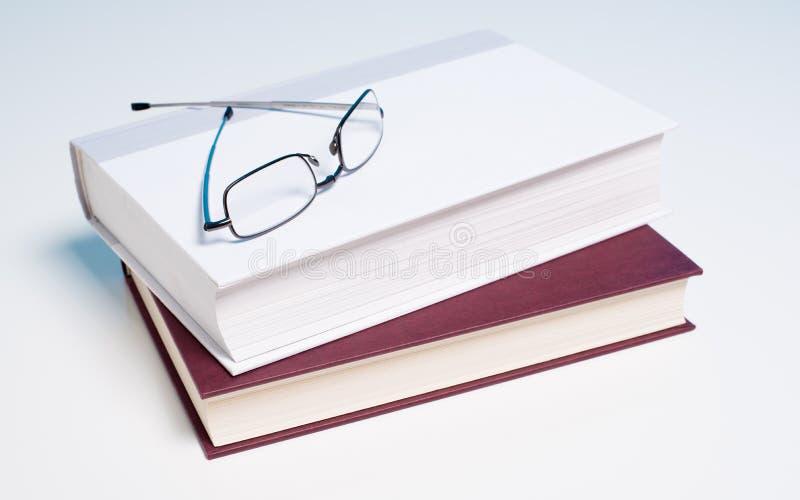 Bücher und Lesebrille auf Weiß lizenzfreie stockbilder