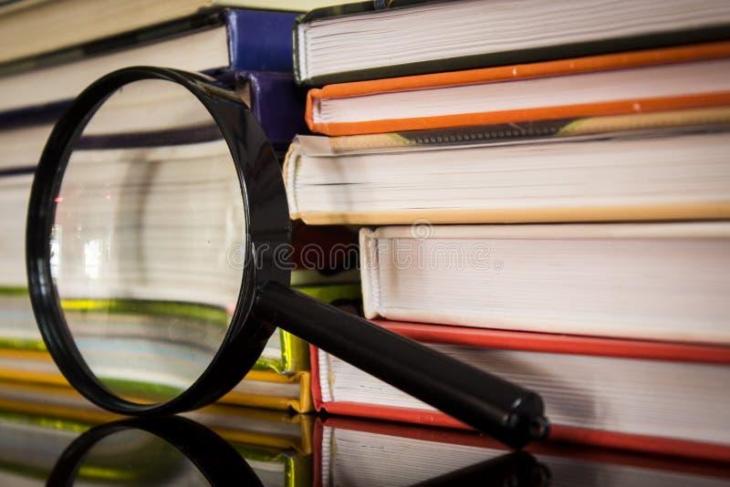 Bücher und Vergrößerungsglas stockbilder