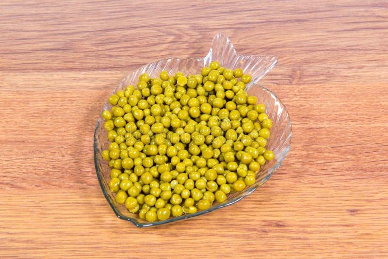 In Büchsen konservierte grüne Erbsen in einer Glasplatte in Form von Fischnahaufnahme auf dem Tisch stockfotos