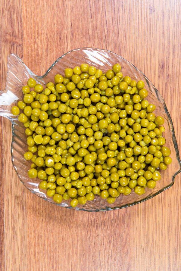 In Büchsen konservierte grüne Erbsen in einer Glasplatte in Form von Fischnahaufnahme auf dem Tisch lizenzfreies stockfoto