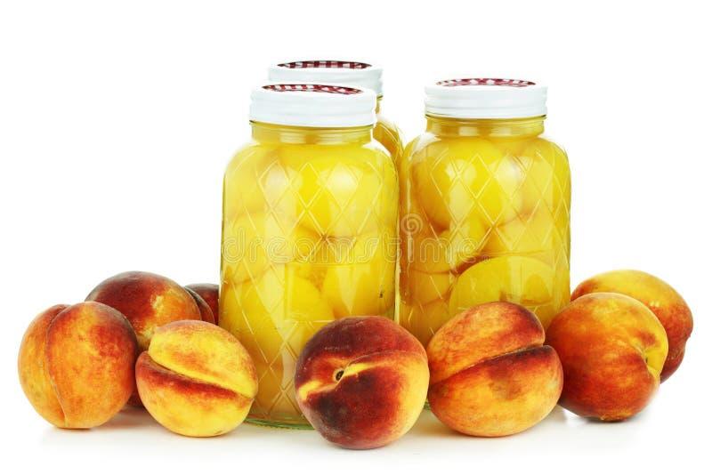 In Büchsen konservierte und frische Pfirsiche stockfotografie