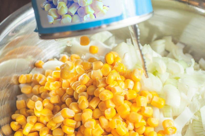 In Büchsen konservierten Mais von einem Glas einer Platte mit der frischen Zwiebel hinzufügen geschnitten für Salat in einer Plat stockfoto