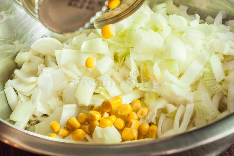 In Büchsen konservierten Mais von einem Glas einer Platte mit der frischen Zwiebel hinzufügen geschnitten für Salat in einer Plat stockbilder