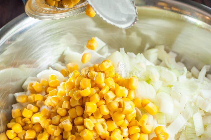 In Büchsen konservierten Mais von einem Glas einer Platte mit der frischen Zwiebel hinzufügen geschnitten für Salat in einer Plat lizenzfreies stockfoto