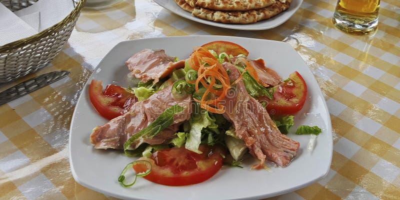 In Büchsen konservierter Thunfischsalat mit grünen Blättern und Tomaten lizenzfreies stockfoto