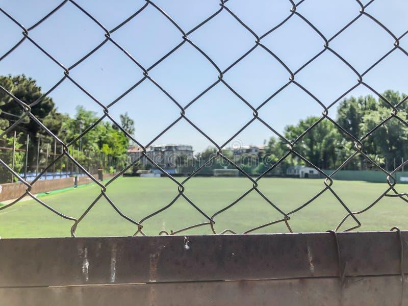 Bügeln Sie das Gitter und ringsum das Fußballstadion zwischen Wohngebäuden fechten Frühjahr in der Stadt stockfotografie