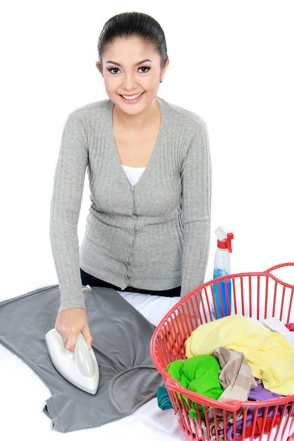 Bügelnde Kleidung der Frau stockfotografie