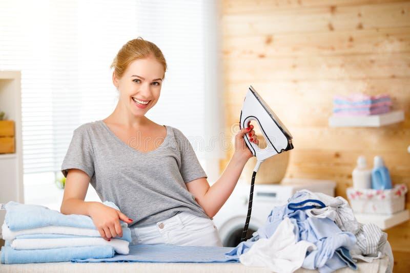Bügelnde Kleidung der glücklichen Frauenhausfrau in der Wäscherei zu Hause stockbild
