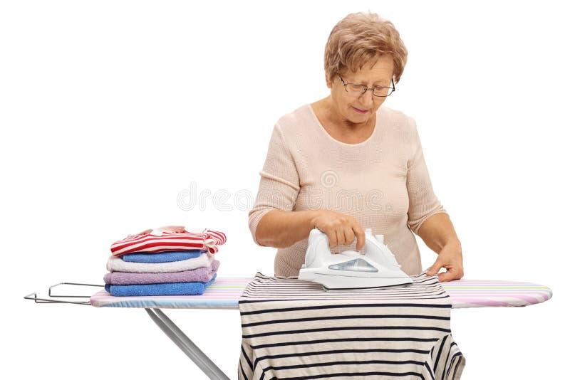 Bügelnde Kleidung der reifen Frau auf einem Bügelbrett stockbilder