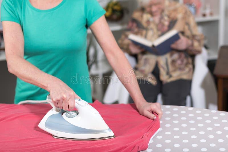 Bügelnde Kleidung des Haupthelfers für eine alte Frau lizenzfreies stockfoto