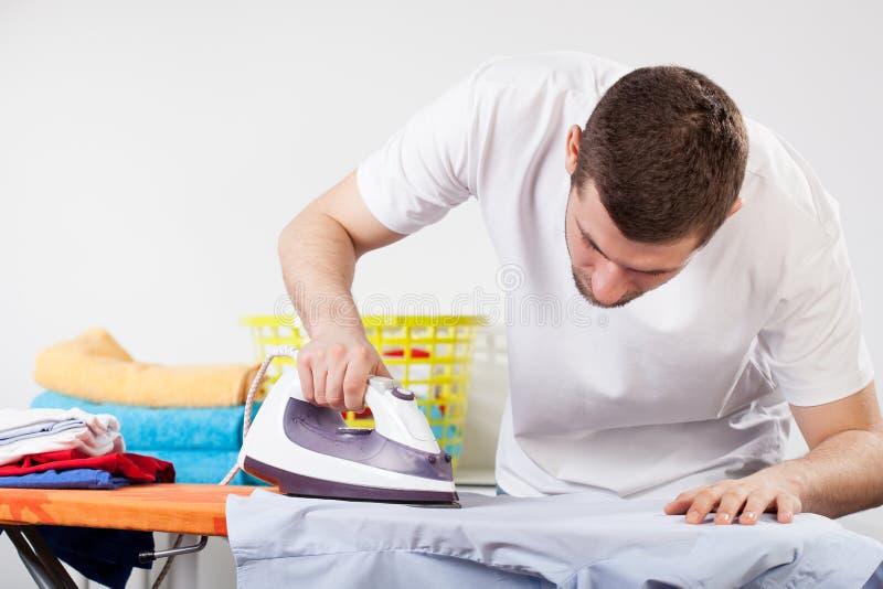 Bügelnde Kleidung des Mannes lizenzfreies stockfoto