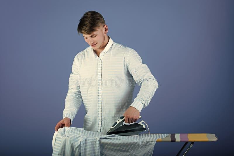 Bügelnde Kleidung des Mannes Hausarbeit- und Modekonzept stockbilder