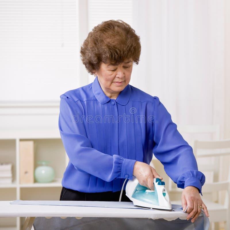 Bügelnde Wäscherei der Hausfrau stockbilder