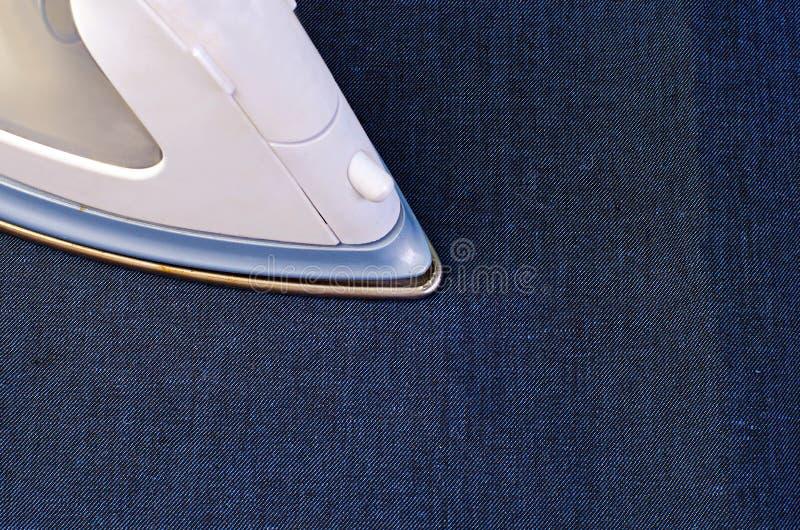 Bügelnder Jeansstoff stockbilder