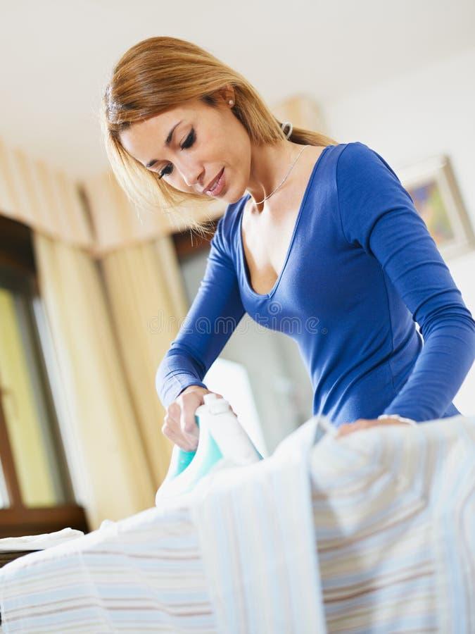 Bügelndes Hemd der Frau lizenzfreie stockfotografie