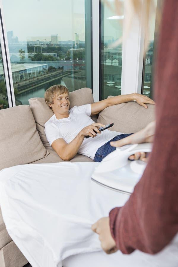 Bügelndes Hemd der Frau während glücklicher Mann, der zu Hause auf Sofa fernsieht