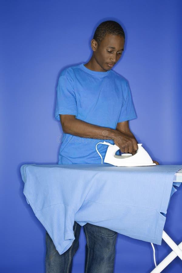 Bügelndes Hemd des jugendlich Jungen. lizenzfreie stockfotografie