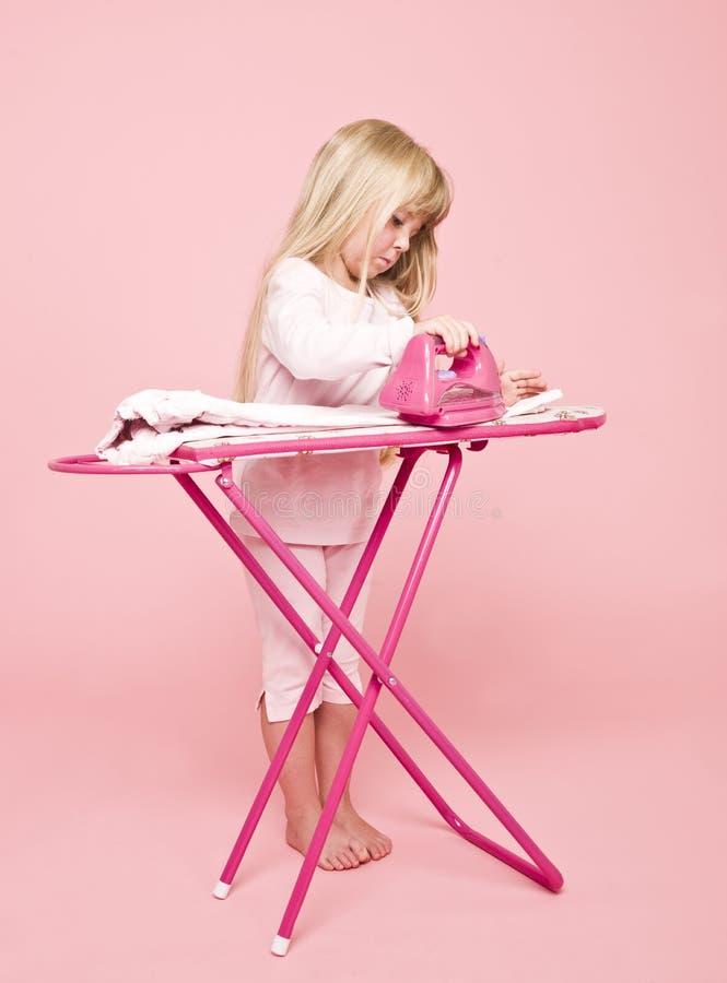 Bügelndes Kleid des kleinen Mädchens stockfoto